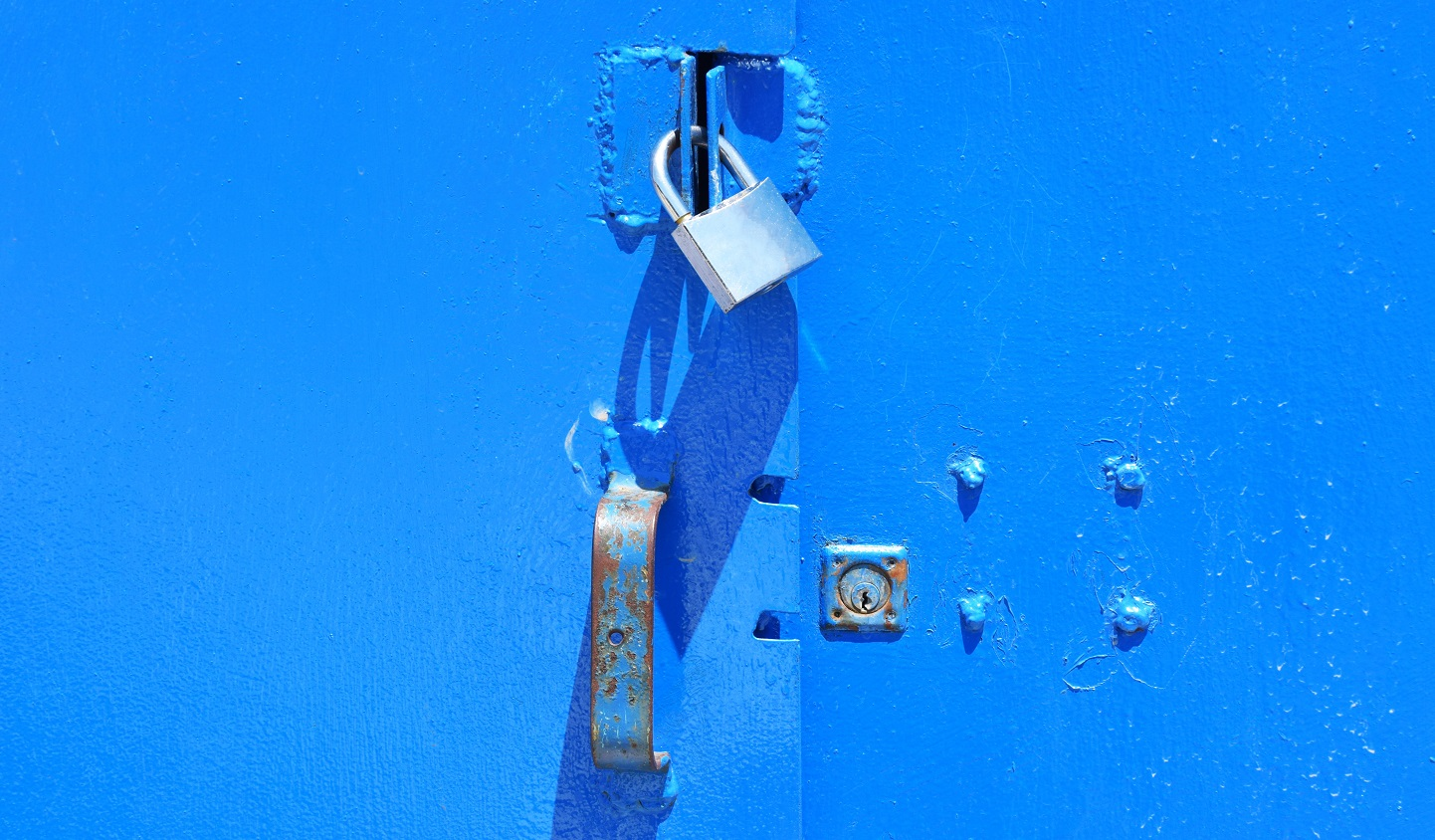 An image of a padlock being used to secure a blue metal door