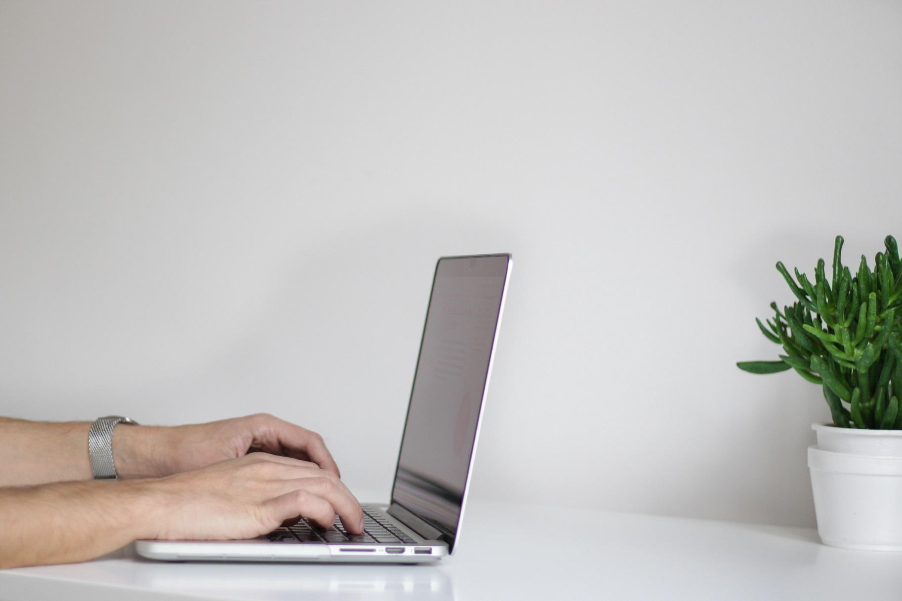 A picture of someone's hands on a laptop keyboard