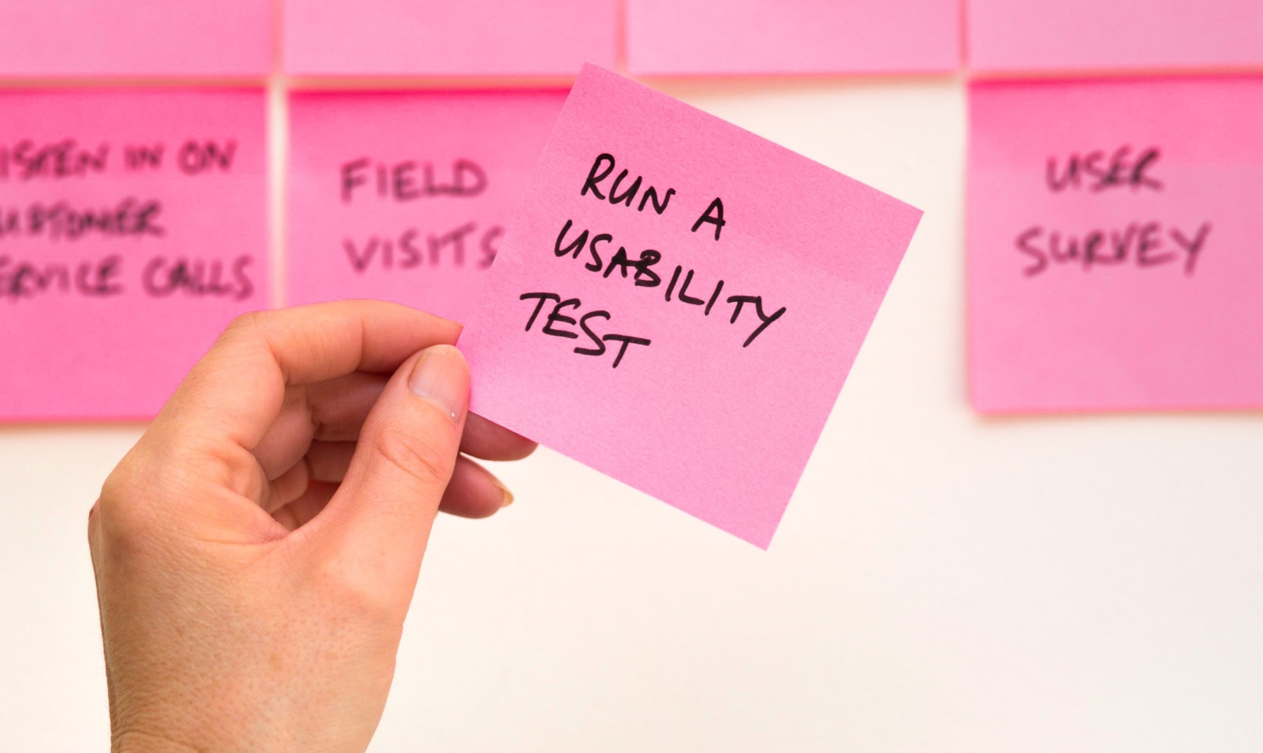 A hand holding a note making reference to running a usability test