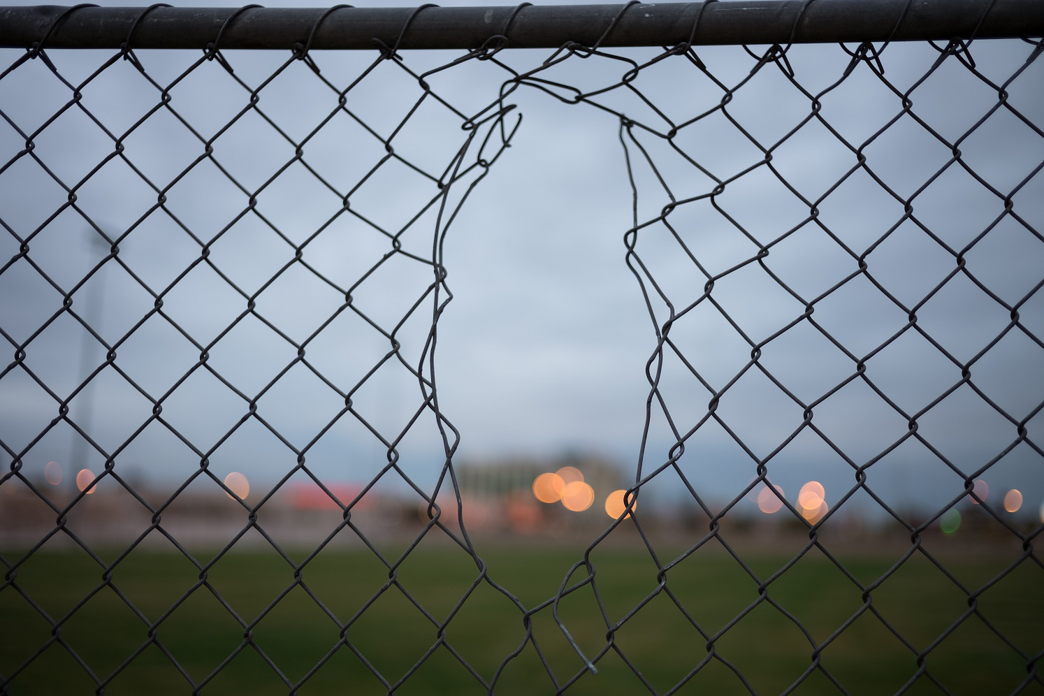 An image showing a large hole in a perimeter fence