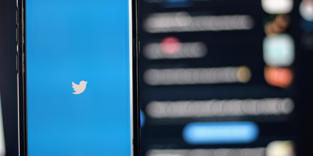 An image of a phone with the Twitter Logo in front of an abstract background